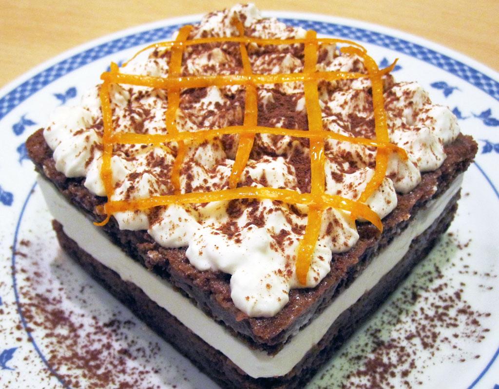 Torta a doppio strato con pan di spagna al cacao, bagna all'arancia e panna di cocco