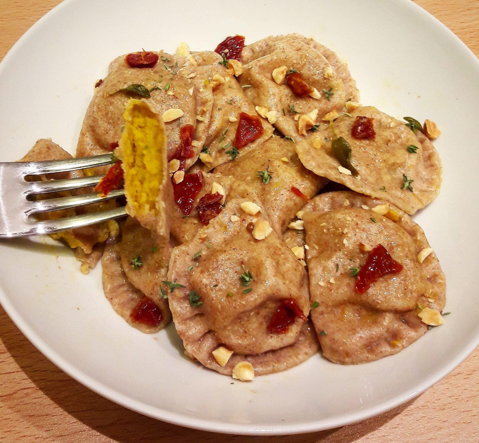 Ravioli di farro ripieni di zucca e ceci al timo con nocciole e pomodori secchi