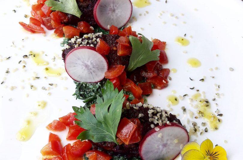 Quenelle di carote viola all'açai su pesto di canapa al prezzemolo e spirulina, con dadolata di pomodori alla curcuma